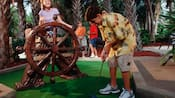 A girl sits on a ship's wheel that obstructs a golf hole, as her brother putts