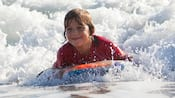 A smiling boy rides a bodyboard in low surf
