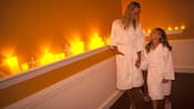 A mother and daughter smile at each other from side-by-side pedicure spa chairs