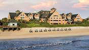 Umbrellas and beach chairs line the beach in front of a resort hotel