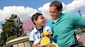 A father smiles down at his enthusiastic young son who is holding tightly to a Donald Duck plush