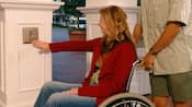 A guest in a wheelchair activates an automatic door opener
