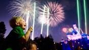 Un niño se sienta sobre los hombros de su papá y contempla maravillado los fantásticos fuegos artificiales de Disneyland