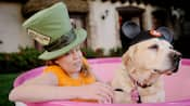 Una niña con impedimentos visuales disfruta de la atracción Mad Tea Party con su perro guía