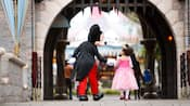 A female Guest dressed as a Disney Princess walks under a drawbridge while holding hands with Mickey