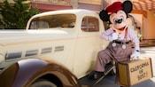 Un Mickey que vende periódicos posa el pie en el estribo de un automóvil clásico en Buena Vista Street