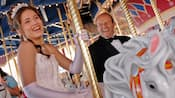 A young lady, in gown, gloves and tiara, rides the carousel during her Disneyland Quinceañera