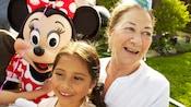 Una niña y su abuela sonríen mientras Minnie Mouse se une a su fiesta de cumpleaños en Disneyland Resort