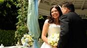 Una novia y un novio caminan tomados de la mano frente al Castillo en la víspera de su casamiento en Disneyland Park