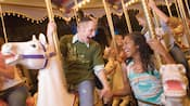 Two teens on carousel horses hold hands and celebrate during Disneyland Resort Grad Nite