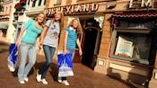 Three women walk down Main Street, U.S.A. with shopping bags.