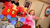 Un hermano y una hermana sonríen al toparse con una Celebración en la Habitación en su hotel en Disneyland Resort