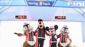 Mickey, Goofy, Chip and Dale stand arm in arm under the finish line archway at the run Disney marathon