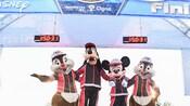 Mickey, Goofy, Chip y Dale se sostienen de los brazos bajo el arco de la meta en la carrera Disney marathon