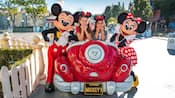 Two girls wearing Mickey ears sit inside a Toontown car and pose with Mickey and Minnie