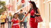 Mother and daughter holding hands and walking together while dressed in Minnie Mouse-themed apparel