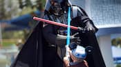 A little boy battles Darth Vader at the Jedi Training Academy
