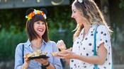 Dos mujeres se ríen mientras saborean delicias del Festival Marketplace
