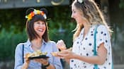 Two women laugh as they enjoy food from the Festival Marketplace