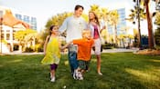 A family of four strolls across a lawn on the grounds of the Disneyland Hotel