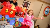 During an in room celebration, a young boy and girl look through Mickey Mouse shopping bags filled with Disney goodies, including hats with Mickey ears, sunglasses and stickers