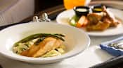 A succulent slice of salmon and 2 asparagus spears sit atop a bed of rice next to another dinner dish