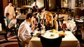 Una pareja brinda con copas de vino durante una elegante cena en Steakhouse 55