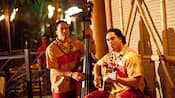 Dos músicos tocan guitarra y contrabajo en la terraza de Trader Sam's Enchanted Tiki Bar