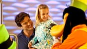 Goofy hace reír a una niña pequeña y a su padre