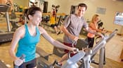 A couple work out on elliptical machines in a well-appointed fitness center
