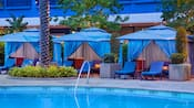 Three poolside cabanas offer privacy and relaxation under draped canopies