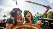 Guests dressed as swashbuckling pirates share laughs at the helm of a sailing ship