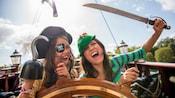 Huéspedes disfrazados de intrépidos piratas riéndose junto al timón de un barco