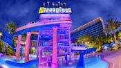 El tobogán y la cascada Monorail brillan en la noche sobre el área de la piscina, rodeada por las torres del hotel