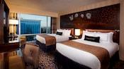 Two queen beds sharing a Sleeping Beauty Castle headboard, a desk, TV-dresser and an easy chair