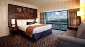 Una cama King Size con una cabecera de Sleeping Beauty Castle frente a un sofá y al lado de una ventana grande