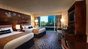 Dos camas Queen Size con cabeceras mágicas, un escritorio, una cómoda con TV, un sofá, además de una ventana panorámica