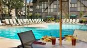 Área de piscina con camastros, sombrillas y mesas