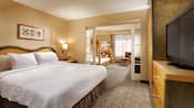 A bedroom with a king bed and, beyond, French doors leading to another room with a twin size bunk bed