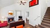 Una suite de dos niveles tipo departamento, que incluye un ático con una escalera y un área de estar con una chimenea, un juego de comedor y una habitación independiente en el piso inferior