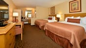 Dos camas matrimoniales frente una cómoda con un televisor, una mesa con dos sillas, además de un tocador