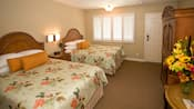 Two queen beds with wooden headboards, a table, armoire and, beyond, windows with shutters