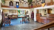 El lobby de Castle Inn cuenta con el mostrador para el registro, ventana de vitral, candelabro de hierro y decoración medieval
