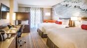 Dos camas Queen Size con cabeceras, mesa de noche con una lampara y área de estar integrada frente a una cómoda, un escritorio con silla, un televisor fijado en la pared y literas dobles