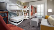 Two queen beds, a desk with an office chair and, beyond, an easy chair and window