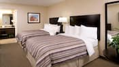 Premier room has 2 queen beds with headboards and a center nightstand with lamp