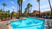 La piscina generosa tiene un amplio espacio de descanso, tumbonas y palmeras