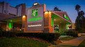 Follaje muy cuidado junto a la entrada cubierta a Holiday Inn Hotel & Suites