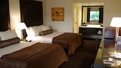Dos camas con almohadones y cabeceras frente a un escritorio y, atrás, un área de tocador