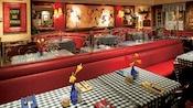 Un restaurante con mesas de banca y un anuncio en la pared que dice Café De Paris